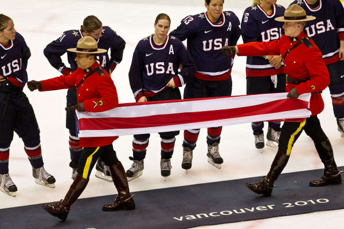 The US flag is carried past USA players including USA's Jenny Potter, center, and Julie Chu during the medals ceremony after the USA lost to Canada in the women's gold medal hockey game.