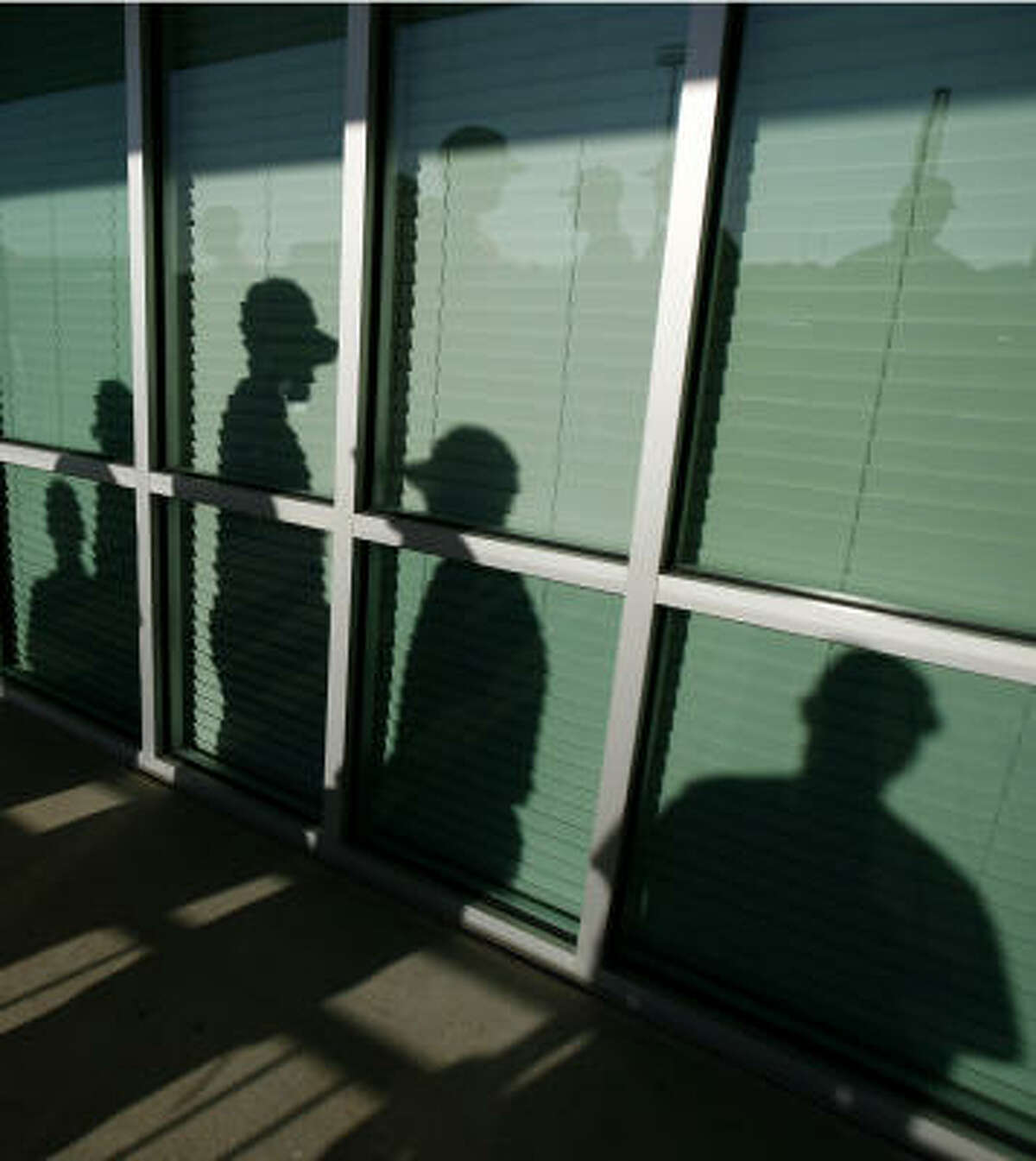 The shadows of Astros players are seen as they wait in line to be photographed during media day at spring training camp.