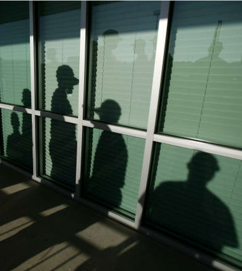 The shadows of Astros players are seen as they wait in line to be photographed during media day at spring training camp. Photo: Julio Cortez, Chronicle