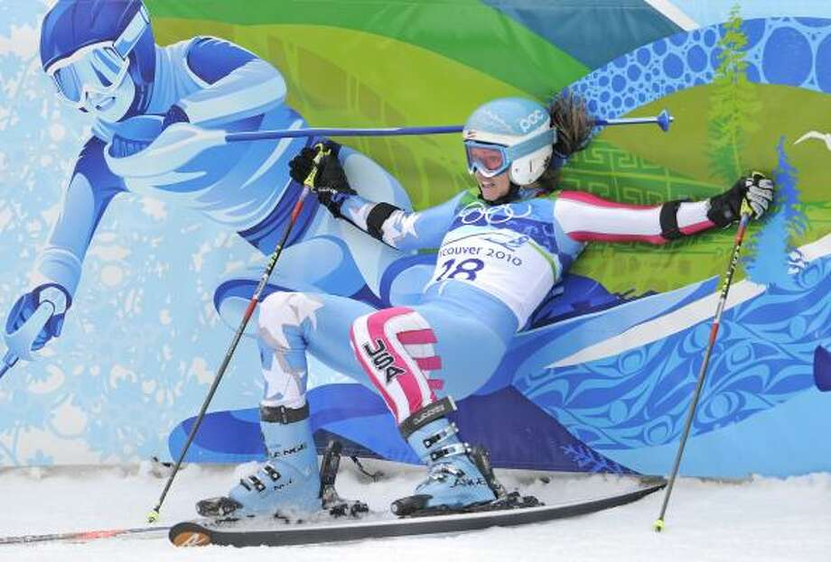 Julia Mancuso of the United States falls on the finish-area fencing after finishing the second run of the women's giant slalom Feb. 25. Mancuso finished in eighth place. Photo: Gero Breloer, AP