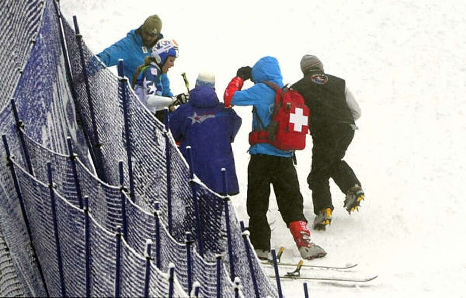Lindsey Vonn (second from left) is helped after she fell. Photo: EMMANUEL DUNAND, AFP/Getty Images