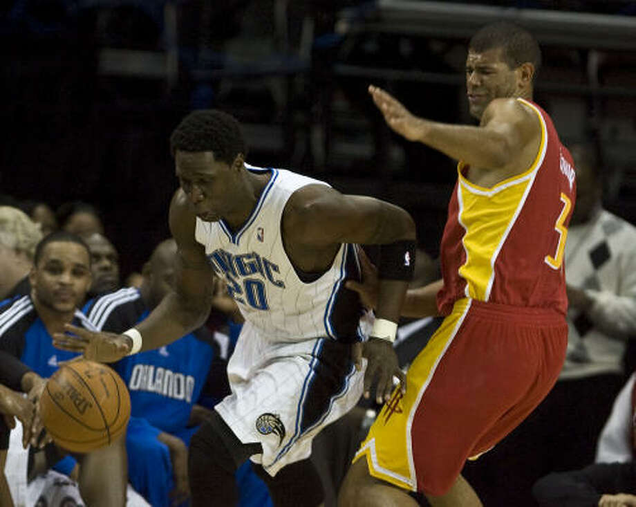The Magic's Mickael Pietrus drives the ball past Shane Battier. Photo: James Nielsen, Chronicle