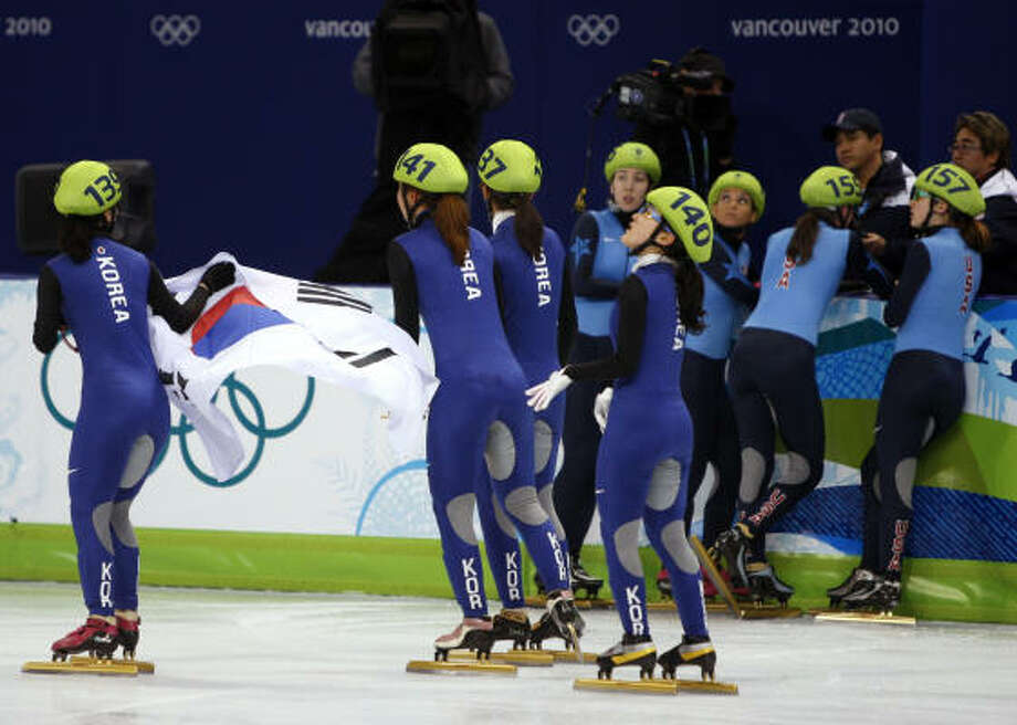 The Republic of Korea team carries the Korean flag past Team USA which thought it finished out of the medals but the Koreans were disqualified giving the bronze to the Americans. Photo: Paul Chinn, Chronicle Olympic Bureau