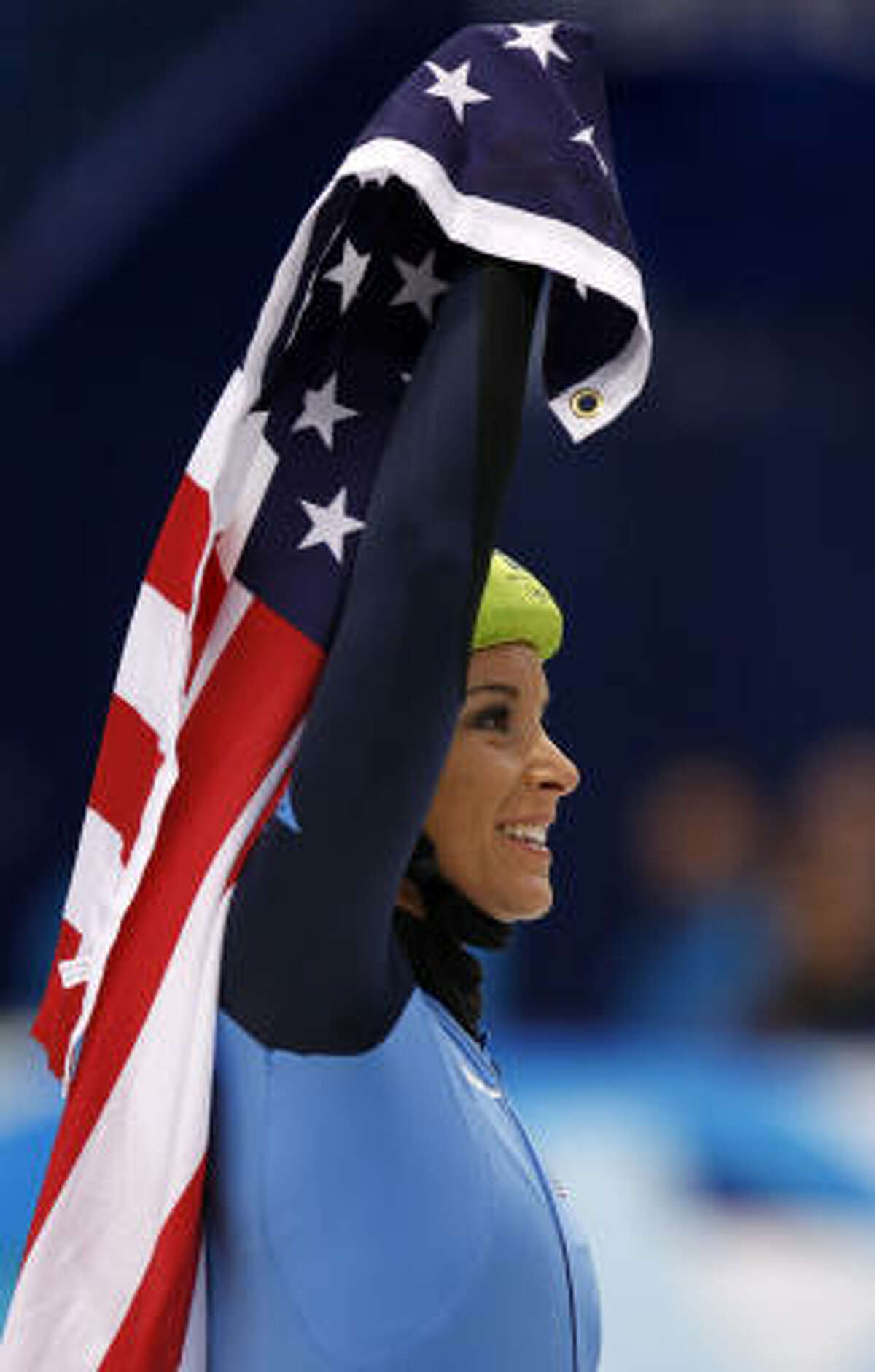 Allison Baver of the United States carries the flag after the Americans took the bronze medal.