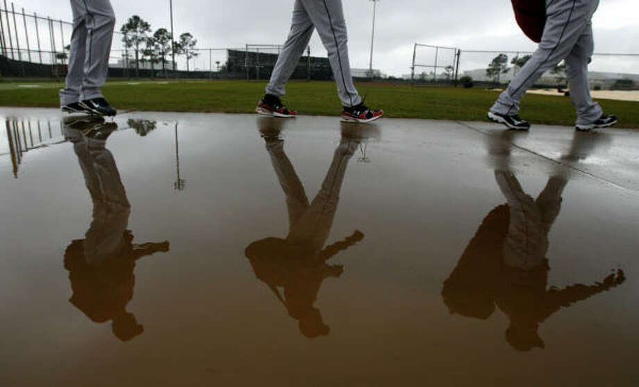 Astros pitchers Jose Valdez, left, and Polin Trinidad, center, walk with catcher Humberto Quintero near a puddle after a morning rain forced the team to stretch indoors. Photo: Julio Cortez, Chronicle