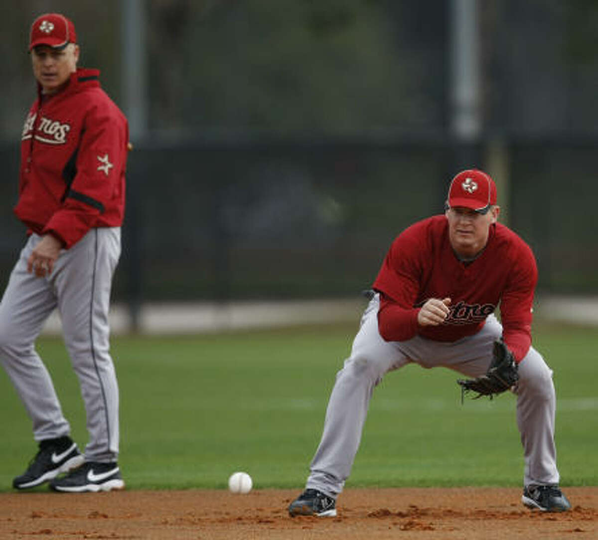 Manager Brad Mills, left, watches as infielder Geoff Blum take grounders at shortstop.