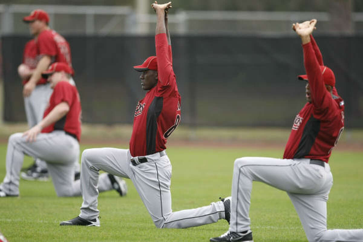 Pitcher Jose Valdez, center, and Fernando Abad stretch to begin the fourth day.