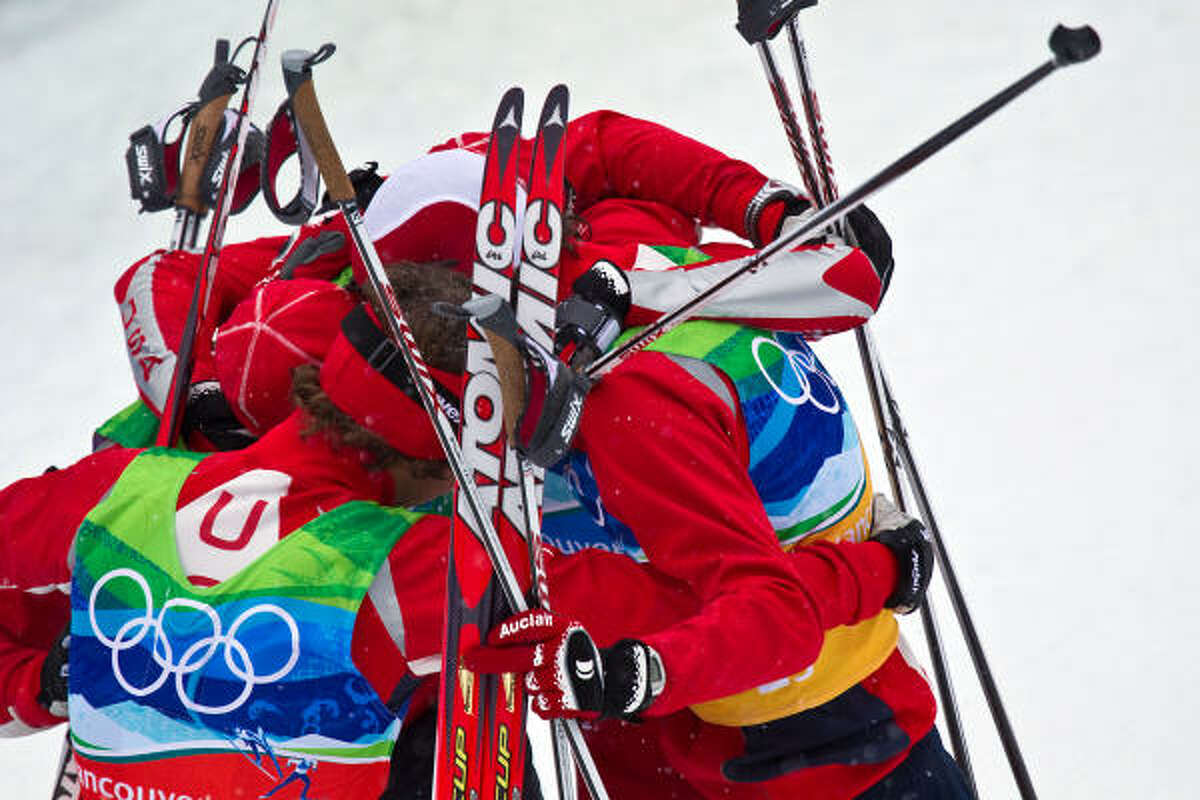 U.S. team members Brett Camerota, left, Todd Lodwick, Johnny Spillane and Bill Demong huddle after winning the silver medal in nordic combined Feb. 23.