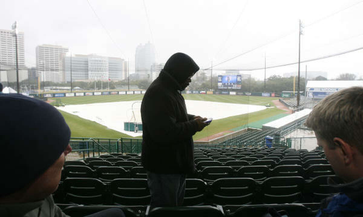 San Diego Padres scout Tim Holt looks at the weather report on his Iphone while (l-r) New York Yankees scouts Steve Boros and Tim Kelly attempt to wait out the rain during a postponed Rice baseball season opener with Texas State at a wet Reckling Park at Rice University. The game was eventually canceled due to the rainy weather.