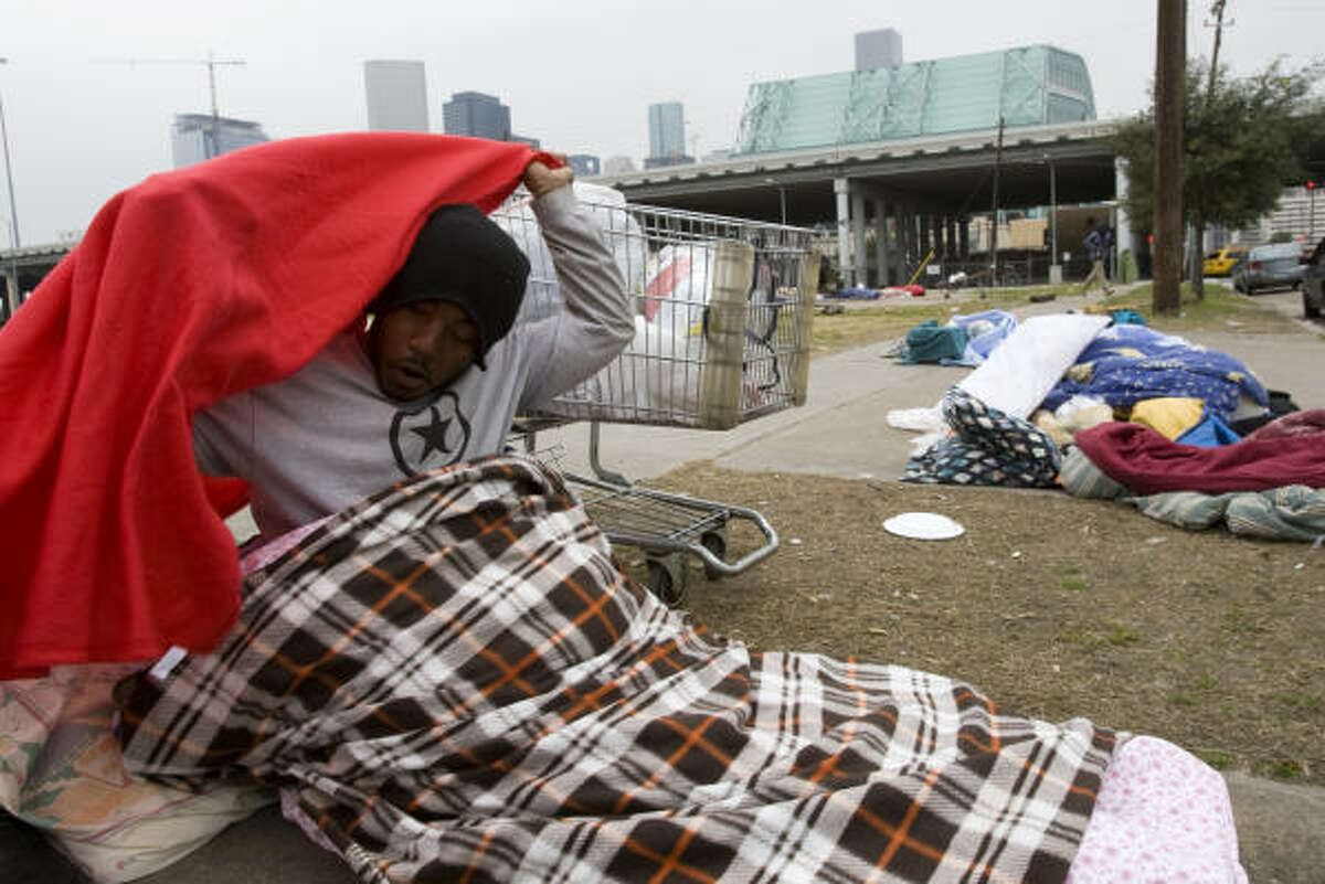A homeless man named Warren covers himself in blankets after getting into a new sleeping bag after receiving it from the Star of Hope in anticipation of the near-freezing temperatures expected in Houston. The Star of Hope handed out more than 100 sleeping bags and several coats to homeless people.