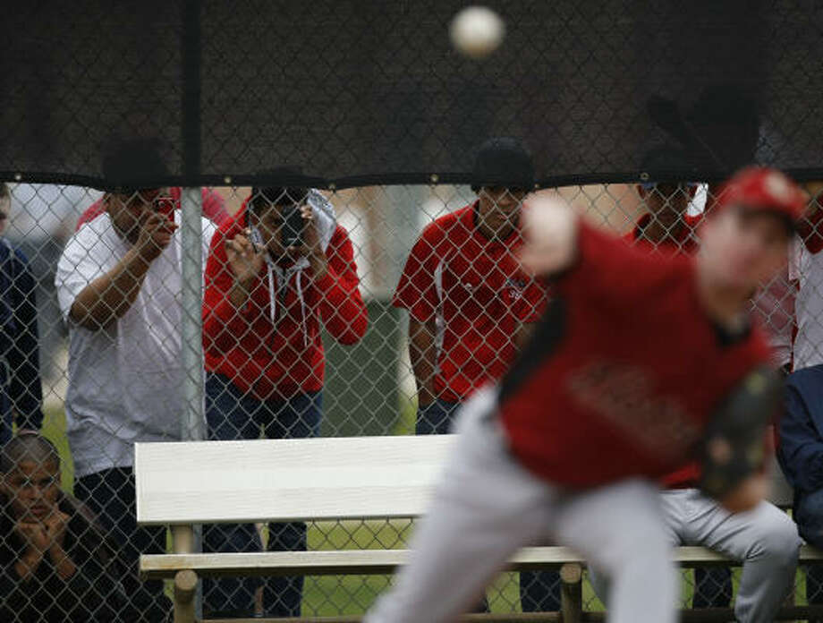 Spectators look through a screen fence as they try to catch a glimpse of Roy Oswalt during his morning workout. Photo: Julio Cortez, Chronicle