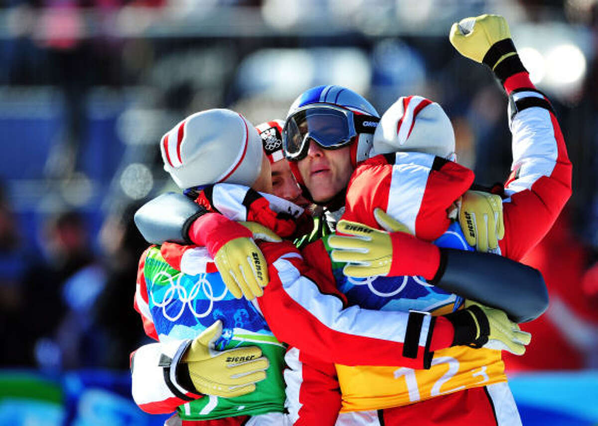 The Austrian celebrates its gold medal in the men's ski jumping team event.