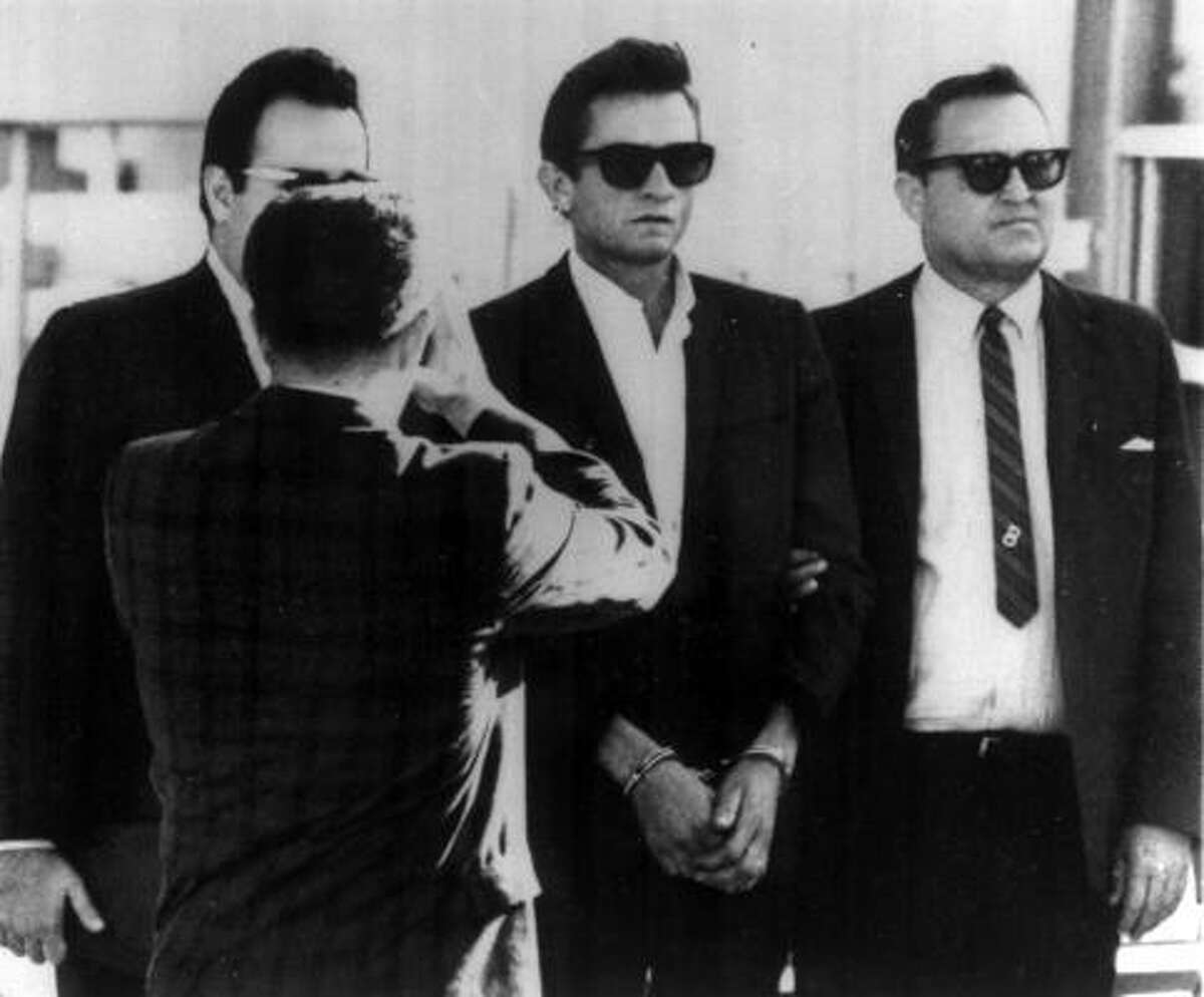 Cash, center, is flanked by a bondsman and a US Marshall as he was transferred from El Paso County Jail to the Federal Courthouse in 1965. The officers suspected that he was smuggling heroin from Mexico, but it was prescription narcotics and amphetamines that the singer had hidden inside his guitar case.