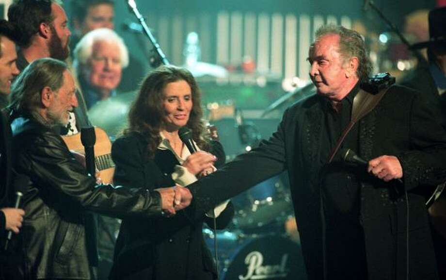 Cash, right, shakes hands with Willie Nelson after performing at the Hammerstein Ballroom in 1999 during a taping of An All-Star Tribute to Johnny Cash. Photo: MARK LENNIHAN, AP