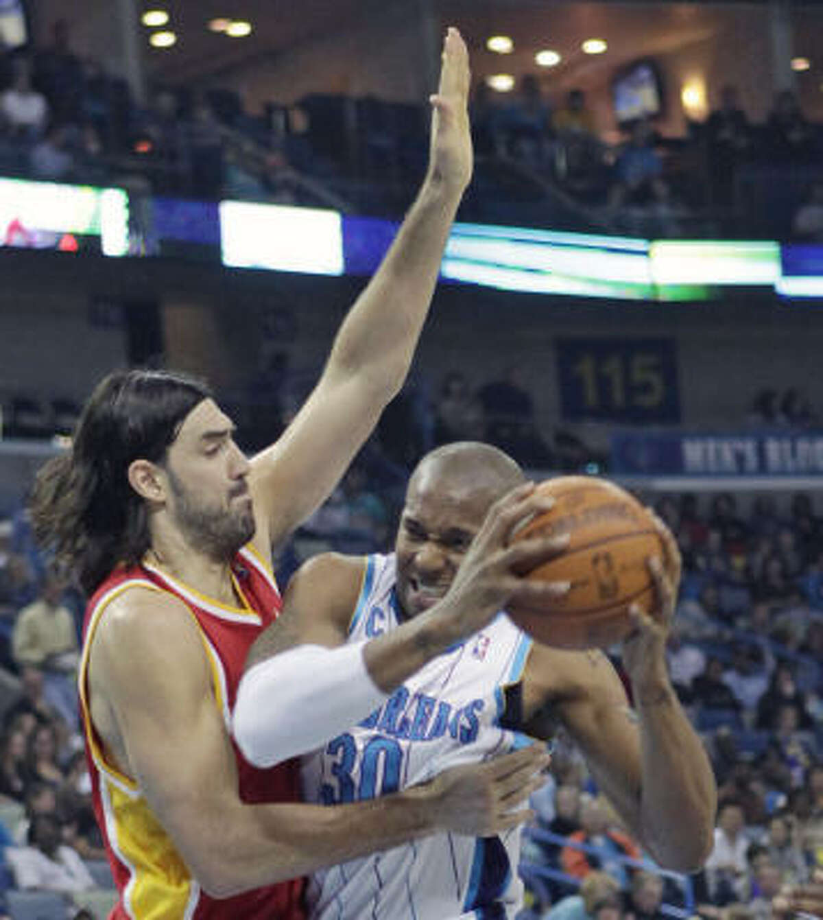 New Orleans Hornets forward David West tries to fight his way around Rockets forward Luis Scola in the first half.