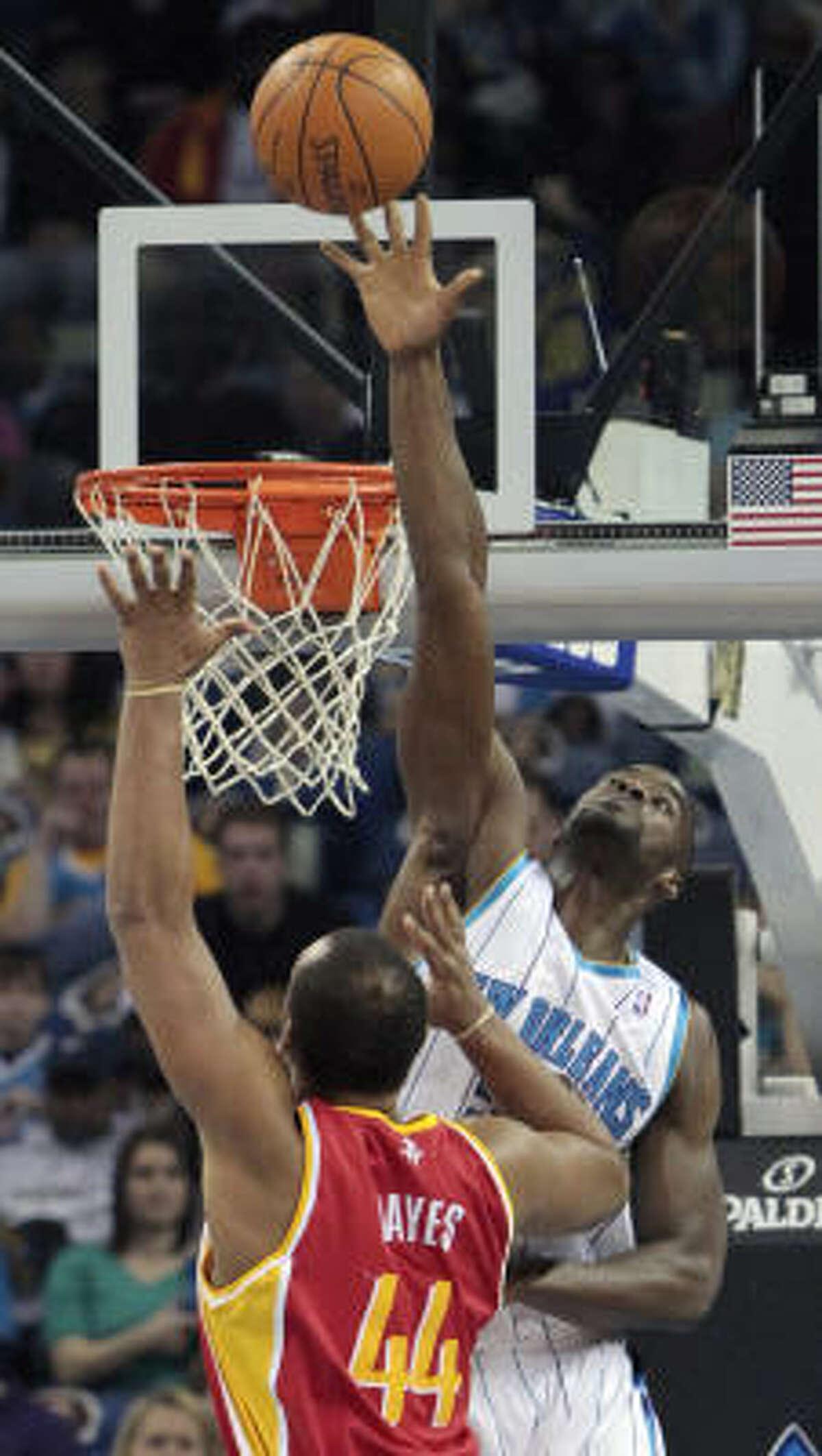New Orleans Hornets center Emeka Okafor, right, blocks the shot of Rockets center Chuck Hayes.