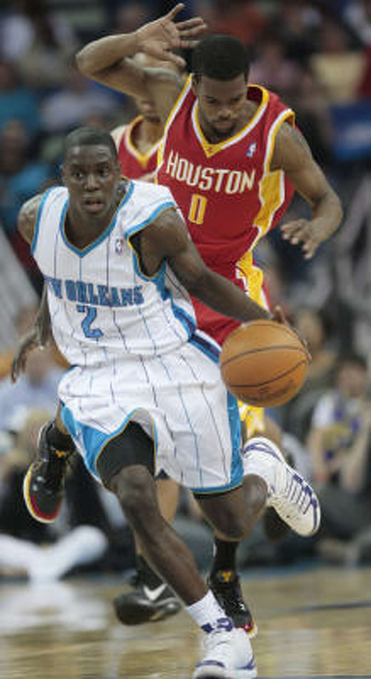 New Orleans Hornets guard Darren Collison leads a fast break as guard Aaron Brooks jumps out of the way.