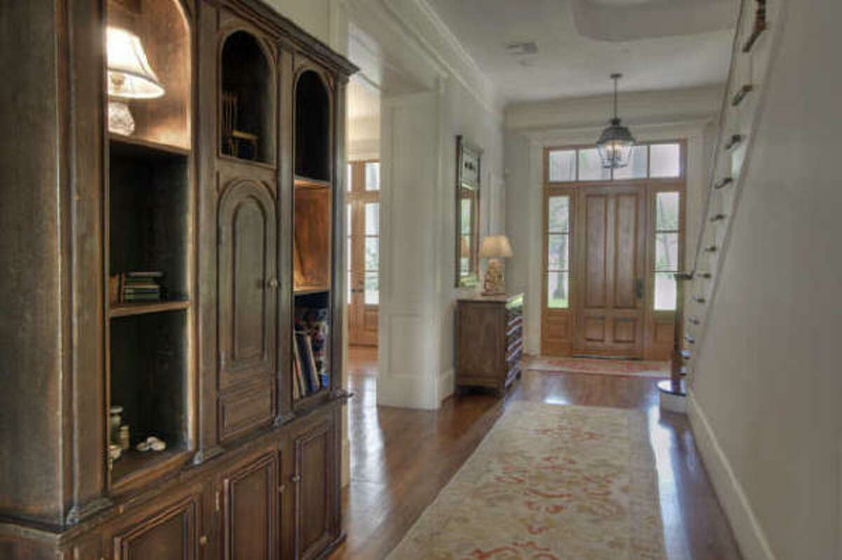 Custom cypress doors set the entrance of this home. Complete with Heart of Pine wood floors, formal powder room with antique finishes, and elevated ceilings.
