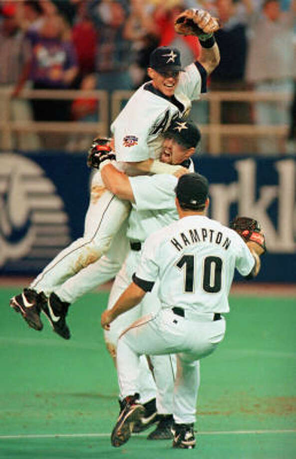 "Jeff Bagwell hoists Craig Biggio as Mike Hampton joins the celebration after the Astros clinched their first division title in 11 years  ""It was just so exciting to finally get into the playoffs,"" Bagwell said.  Hampton pitched a four-hitter in the 9-1 clincher against the Chicago Cubs.  The Astros, under rookie manager Larry Dierker, advanced to face the Atlanta Braves in the NL Division Series. Photo: SMILEY N. POOL, Chronicle"