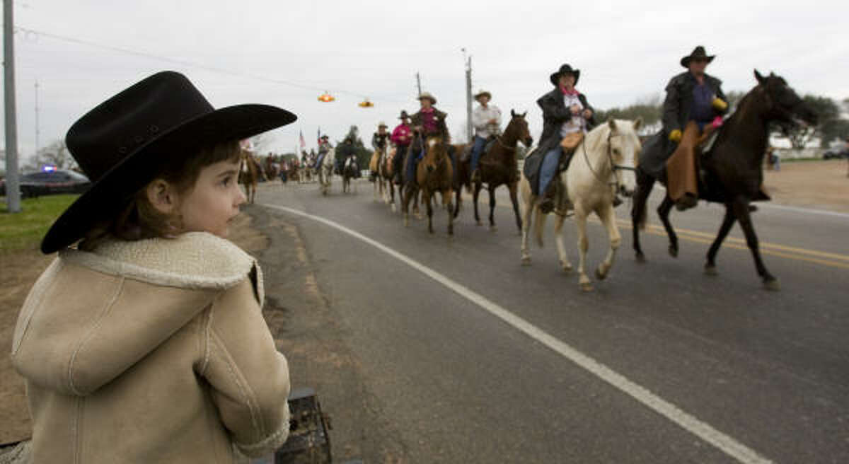 Rylin Kern, of Waller, watches the Salt Grass Trail Riders as they take to the road at the beginning of their ride in Cat Spring.