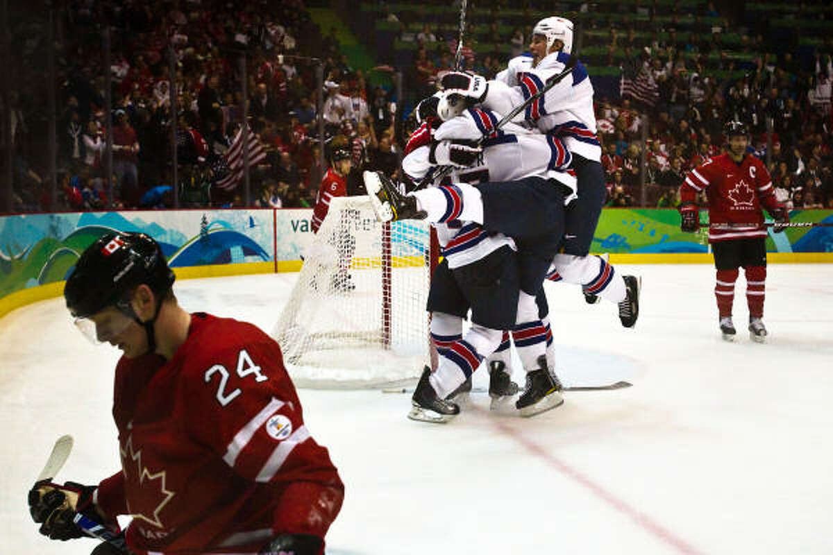 USA players mob Ryan Kesler after his empty net goal in the final minute gave the USA a 5-3 victory over Canada's Corey Perry, left, and his teammates in men's hockey preliminary round action.