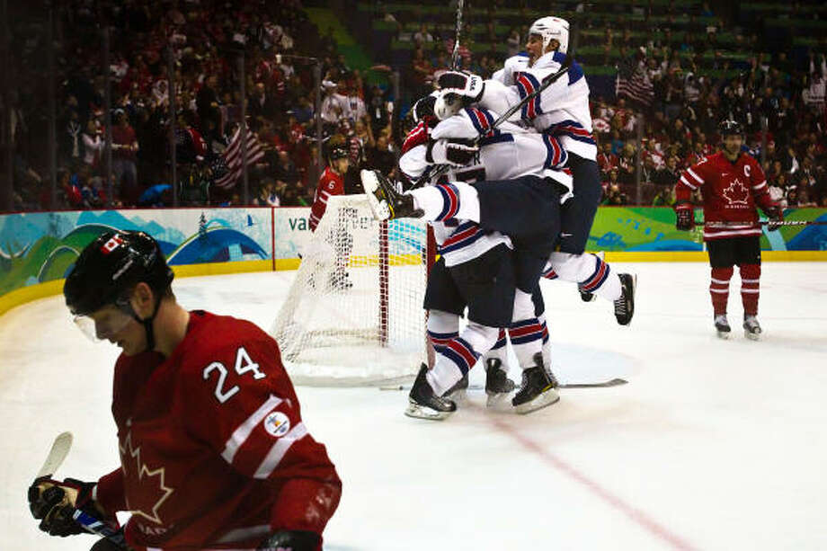 USA players mob Ryan Kesler after his empty net goal in the final minute gave the USA a 5-3 victory over Canada's Corey Perry, left, and his teammates in men's hockey preliminary round action. Photo: Smiley N. Pool, Chronicle Olympic Bureau