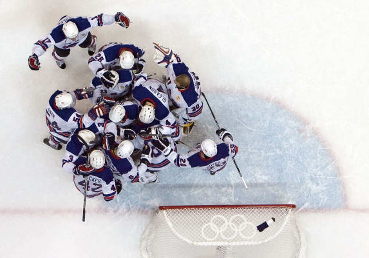 Team USA players celebrate around USA goalie Ryan Miller after a 5-3 victory over Canada.