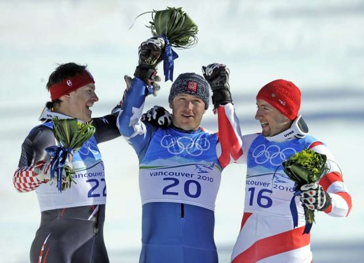 Bode Miller, center, celebrates with silver medalist Ivica Kostelic of Croatia, left, and Switzerland's Silvan Zurbriggen, who won the bronze.
