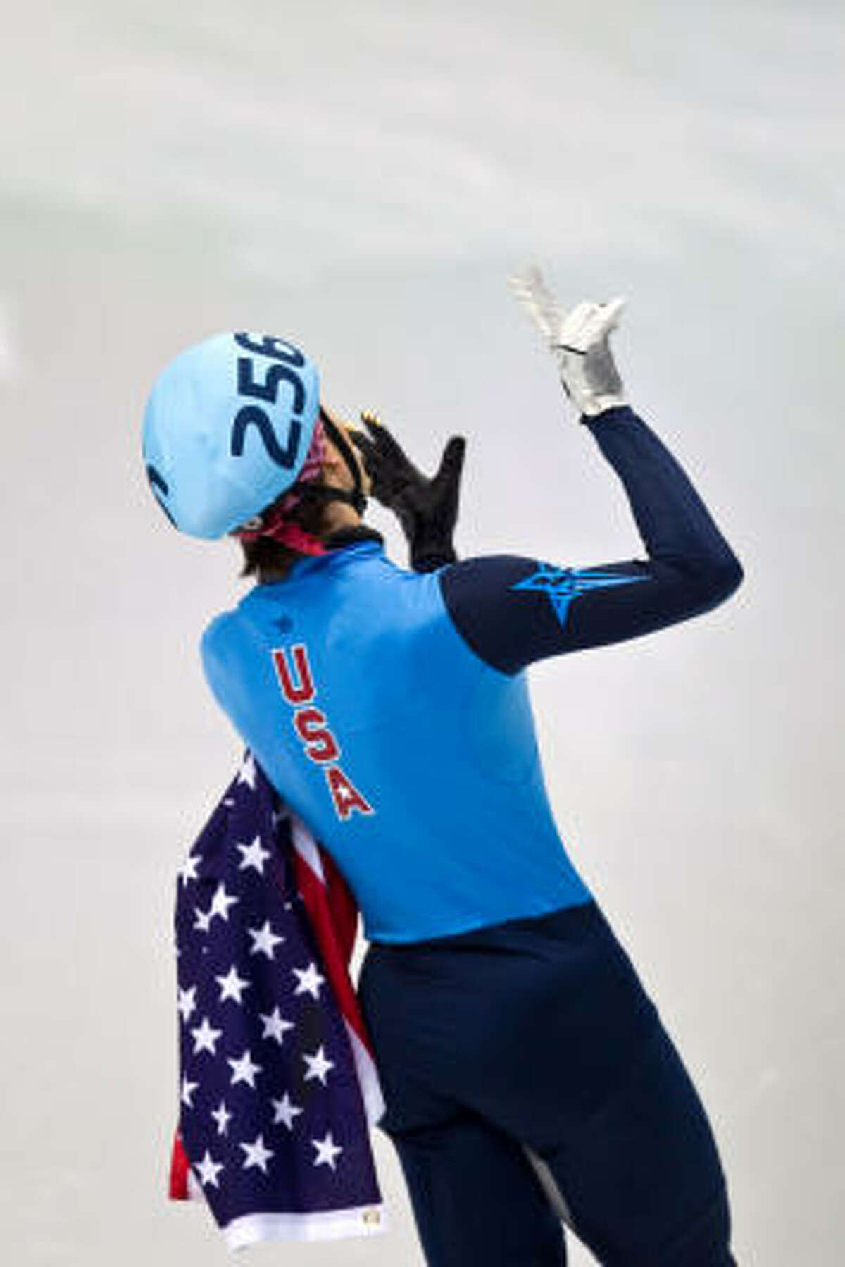 Apolo Anton Ohno holds up seven fingers to the crowd to signify his overall medal count.