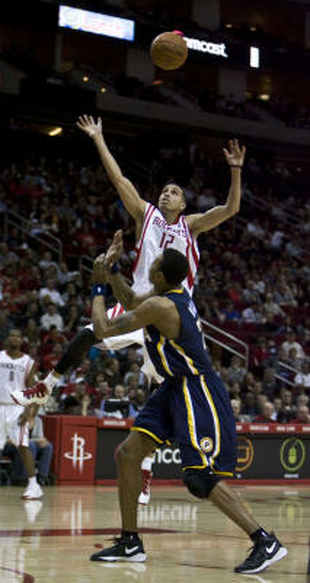 Rockets guard Kevin Martin, who was acquired from Sacramento before Thursday's trade deadline, jumps over Indiana's Brandon Rush for a loose ball in the second quarter.