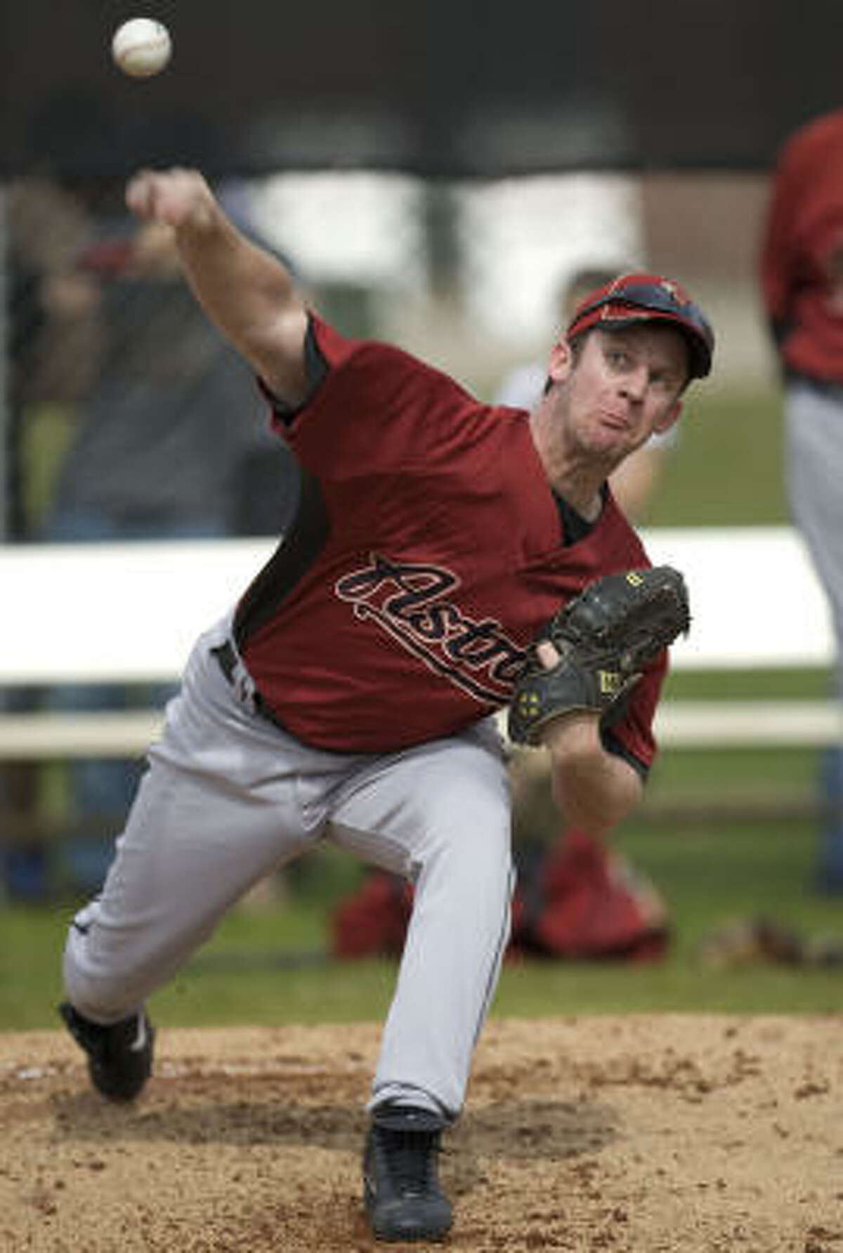 Roy Oswalt tosses a pitch during a workout on the first day of spring training in Kissimmee, Fla.