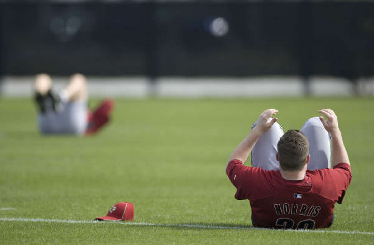 Pitcher Bud Norris stretches before the start of the first day of spring training at Osceola County Stadium.