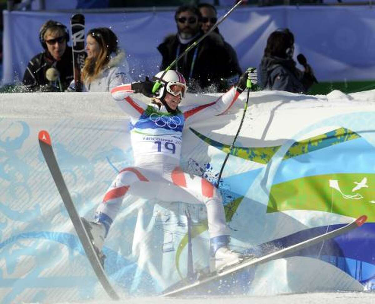 Austria's Andrea Fischbacher finishes her gold medal run with a crash into the finish area safety fence.