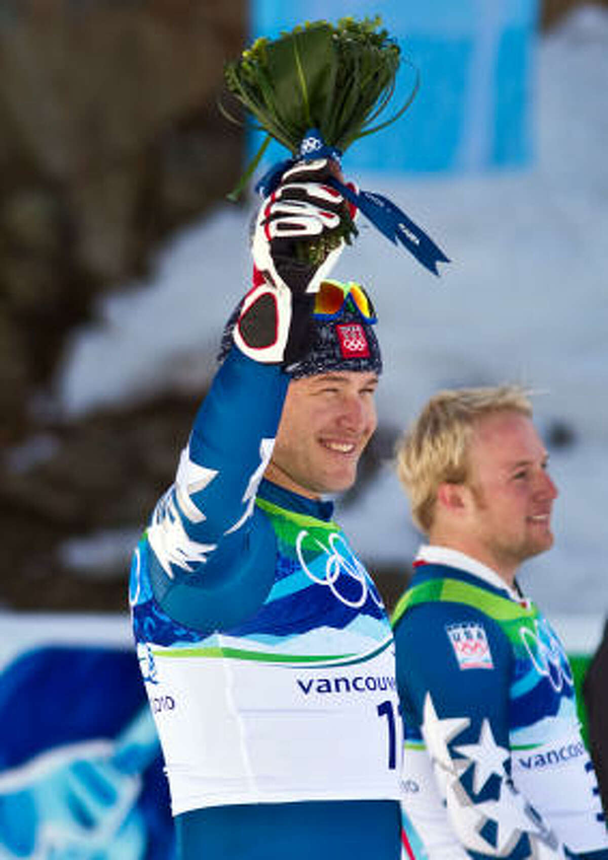 Bode Miller, left, and Andrew Weibrecht of the United States wave from the podium after winning the silver and bronze medals, respectively, in the mens' alpine skiing super-G Feb. 19.