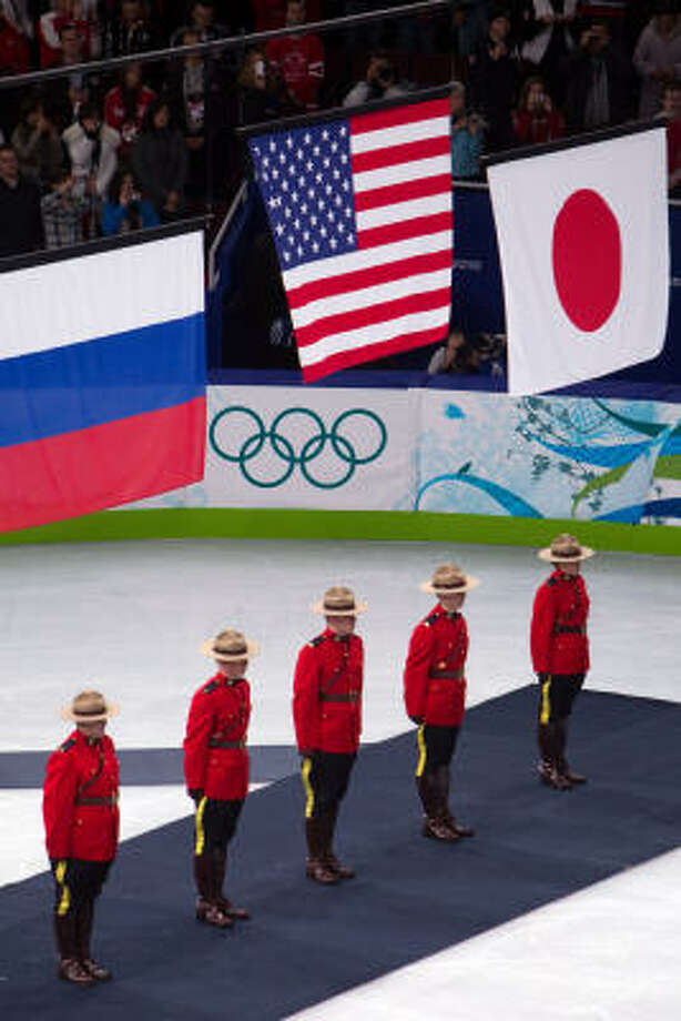 The flags of the USA, Russia and Japan are raised during the medals ceremony. Photo: Smiley N. Pool, Chronicle Olympic Bureau
