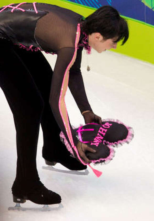 Johnny Weir picks up a heart-shaped pillow with his name on it that was thrown from the stands at Pacific Coliseum. Photo: Smiley N. Pool, Chronicle Olympic Bureau