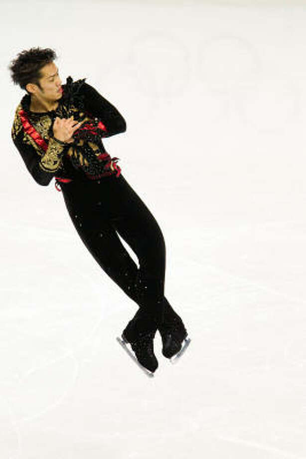 Daisuke Takahashi of Japan hangs in the air during his short program. Photo: Smiley N. Pool, Chronicle Olympic Bureau