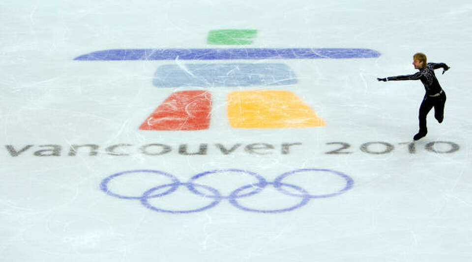 Evgeni Plushenko skates past the logo of the Olympic Games.