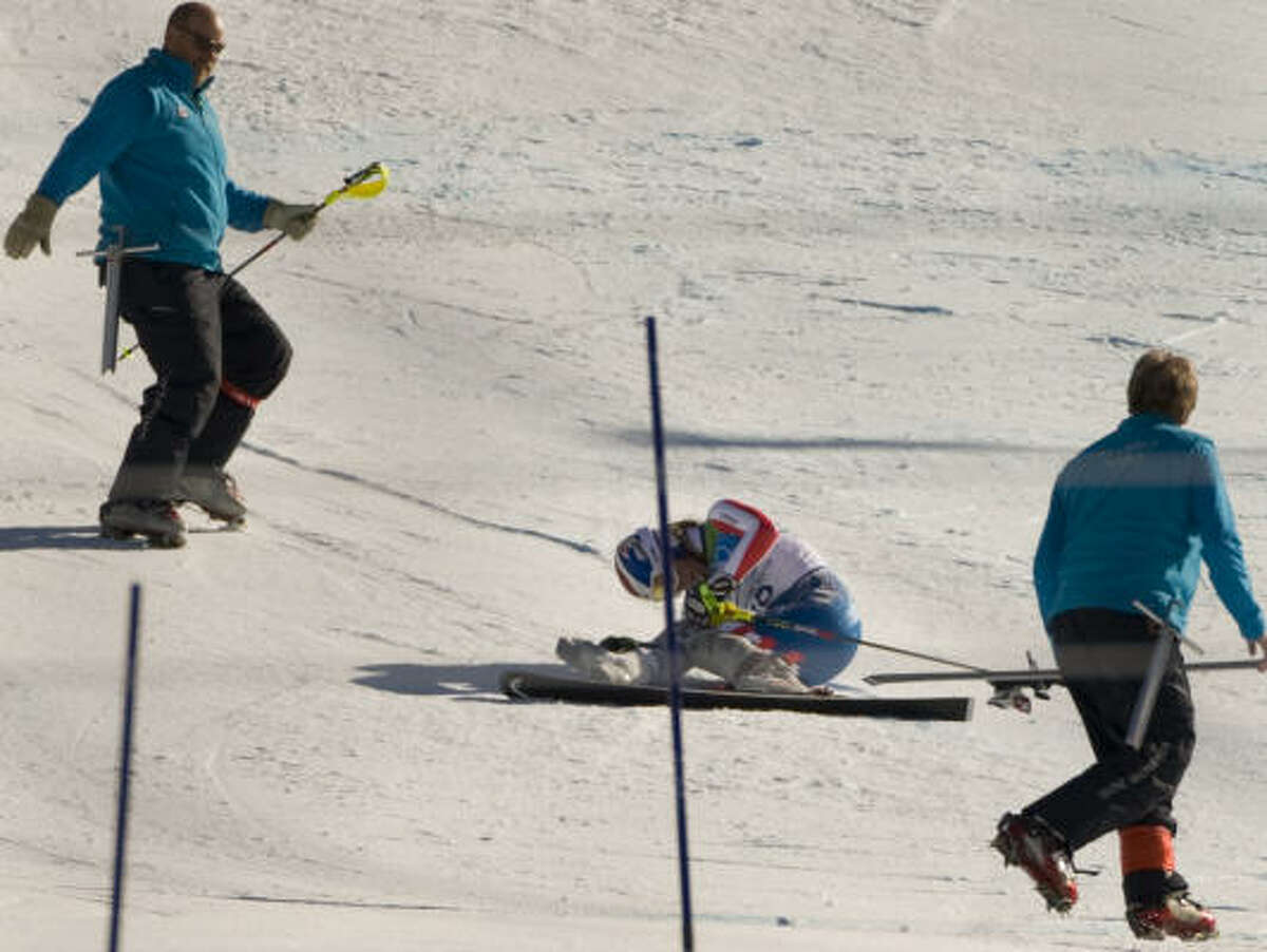 Course workers retrieve a pole and a ski after Lindsey Vonn crashes.