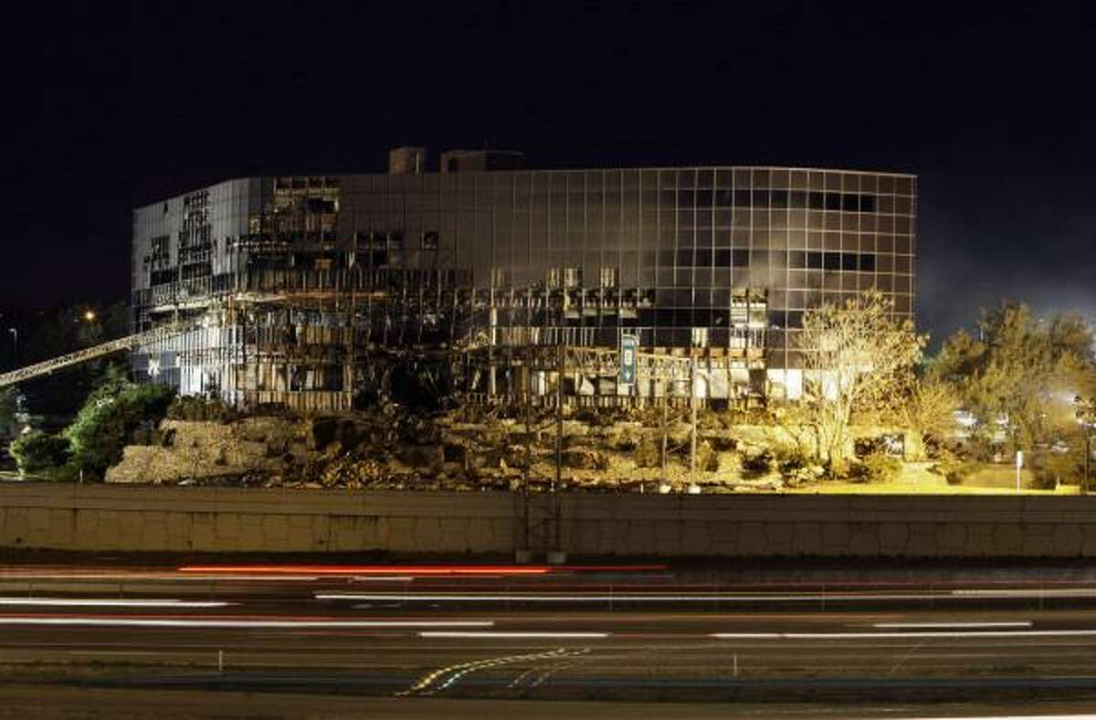 Streaks of light from vehicle traffic are shown in front of the damaged building.
