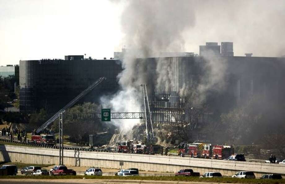 Smoke billows from a seven-story building after a small private plane crashed into the building  in Austin, Texas.  At least two people have been hospitalized since the crash. Photo: Jay Janner, AP