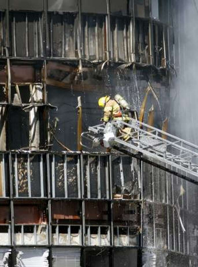 Firefighters work on putting out a fire at the seven-story building. Photo: Jack Plunkett, AP