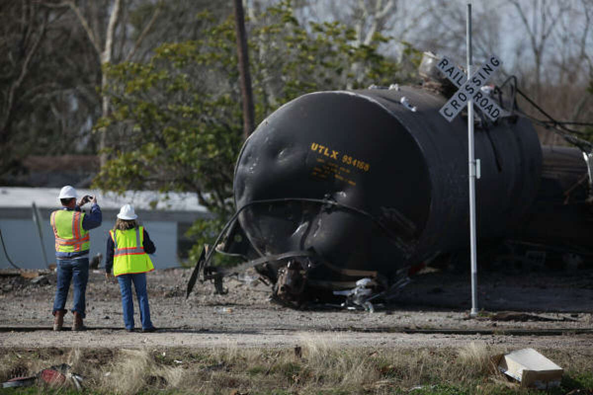 Workers take photos of a derailed tanker, part of a train hauling 21 cars, which derailed near the intersection of FM 646 and Highway 6 where chemicals were spilled on to Highway 6 in Santa Fe, TX. Evacuations were ordered in a one mile radius from the spill due to hazardous chemicals such as propane gas, and liquid asphalt.