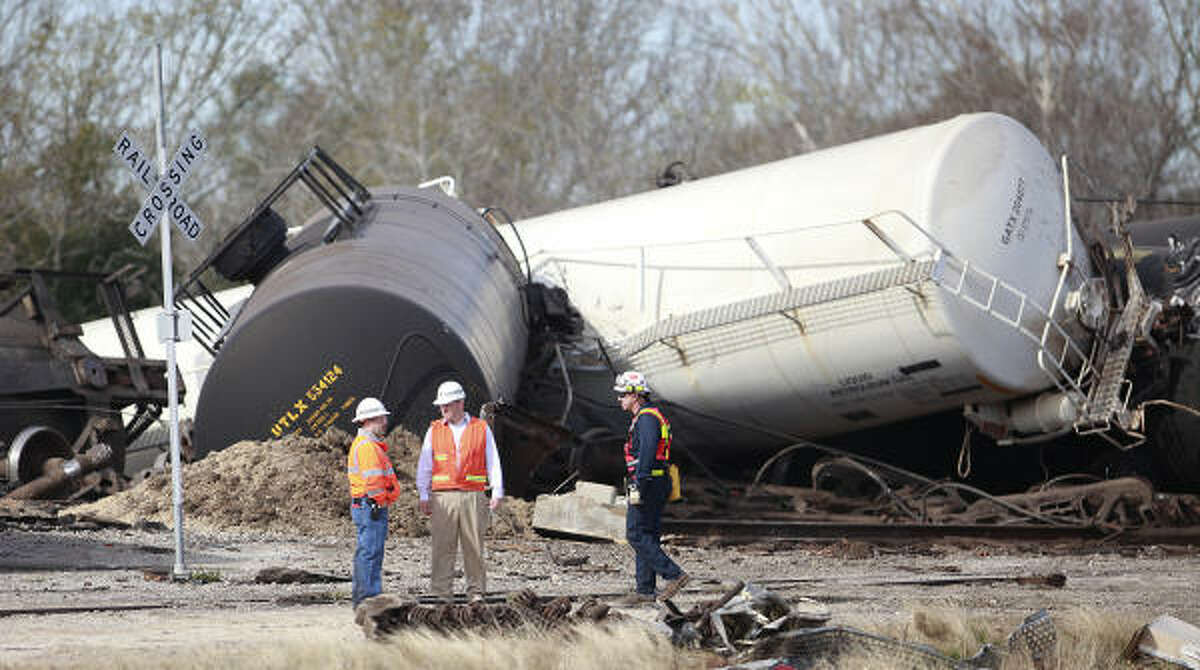 Workers begin the process of cleaning up after a train hauling 21 train cars derailed in Santa Fe, TX. Evacuations were ordered in a one mile radius from the spill, due to hazardous chemicals such as propane gas, and liquid asphalt.