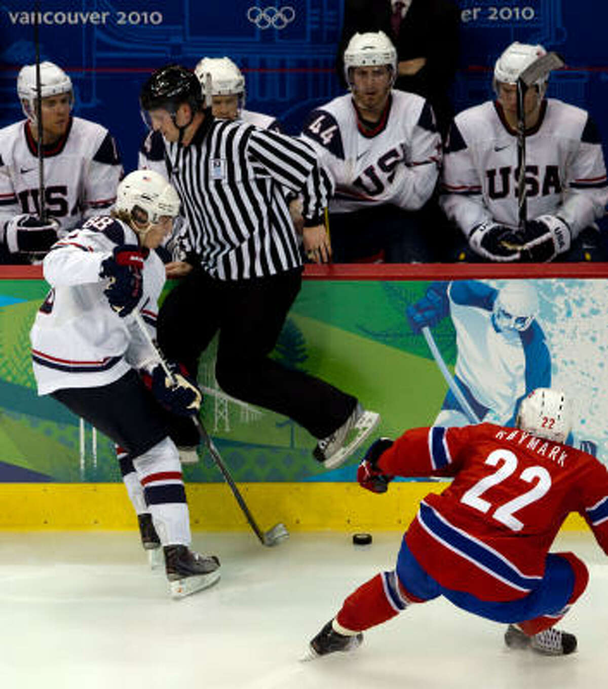 A linesman hops over the puck as USA's Patrick Kane and Norway's Martin Roymark give chase during a preliminary round hockey game. Team USA won 6-1.