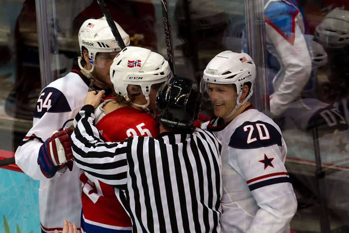An official separates Team USA's Ryan Suter (20) from Norway's Martin Laumann Ylven.