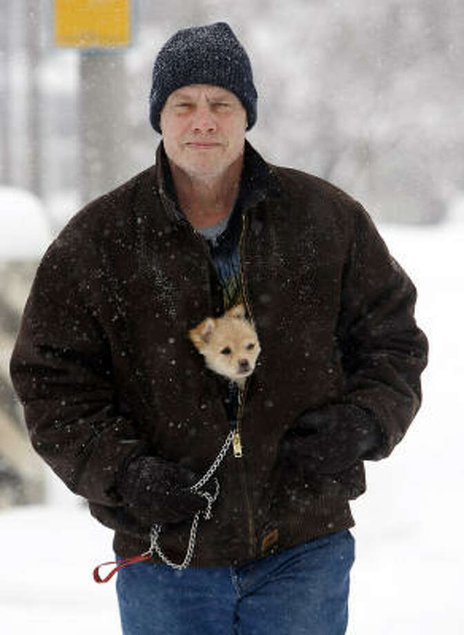 "David Carter of Southgate, Ky., carries a puppy inside his coat to keep her warm as he walks along US 27 in Southgate Feb. 15. Carter said a friend gave him the dog a week ago and he has yet to name her. ""I'm thinking about calling her Trouble,"" he said, ""because every time I open the door she runs outside.""  Share your dog pics. Photo: Patrick Reddy, AP"