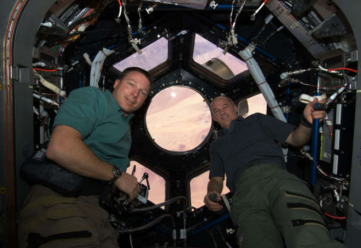 With the windows newly unblocked, astronauts Terry Virts, left, and Jeffrey Williams explore the space station's new feature Wednesday.