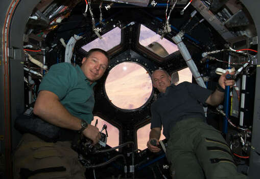 With the windows newly unblocked, astronauts Terry Virts, left, and Jeffrey Williams explore the space station's new feature Wednesday. Photo: Associated Press/NASA