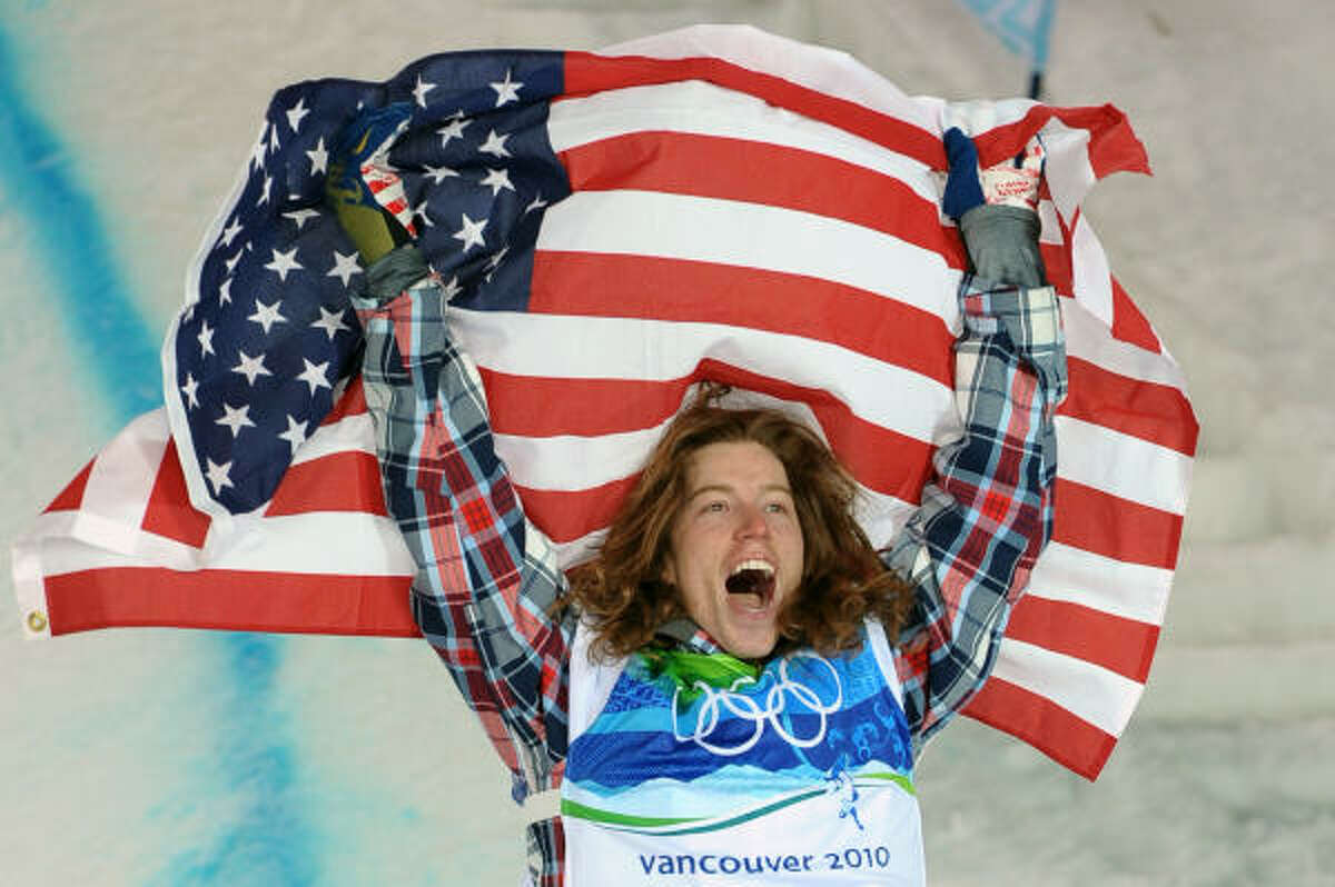 Shaun White holds the American flag in triumph after his victory.